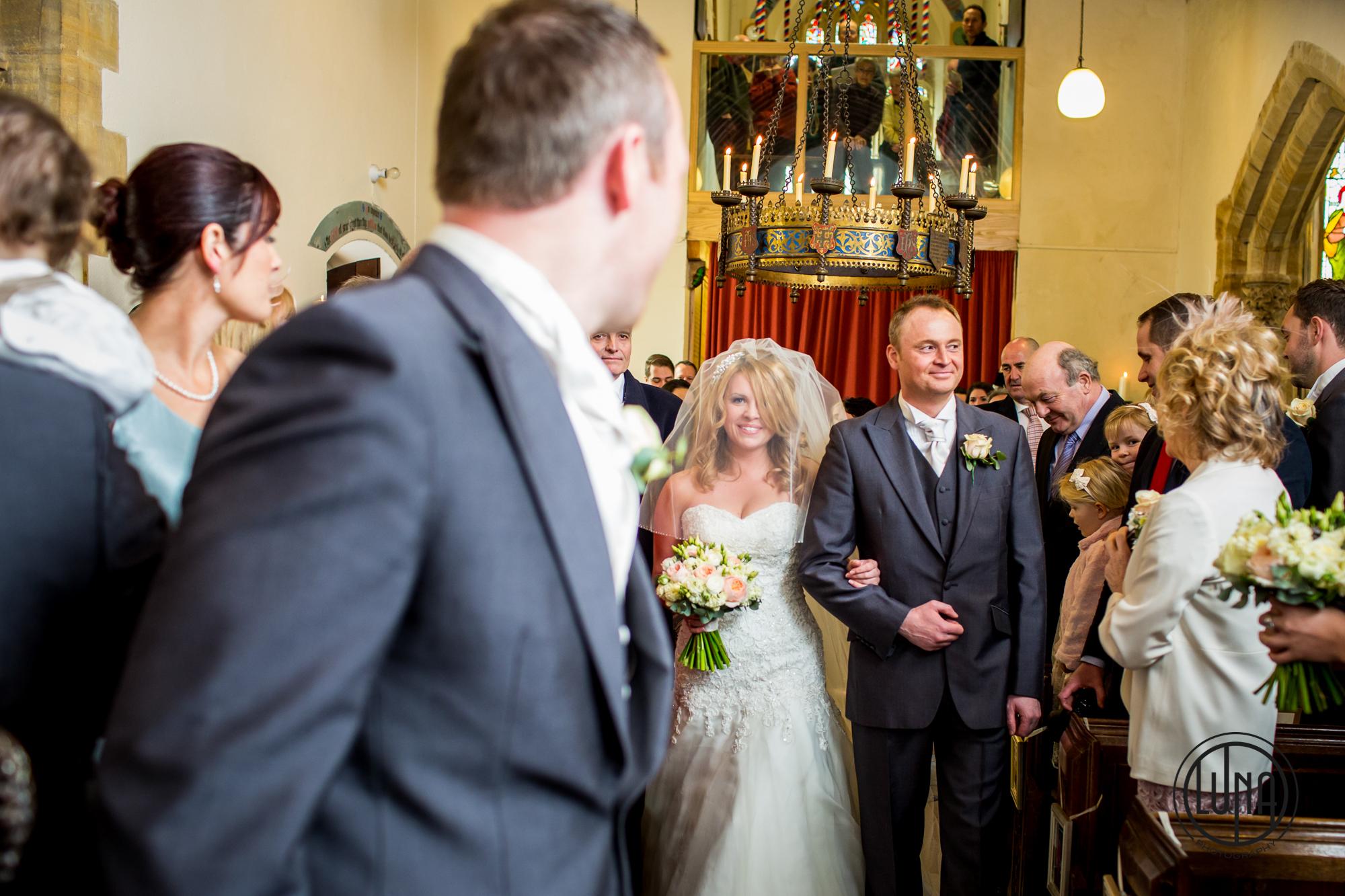 bride walks down aisle at huntsham court
