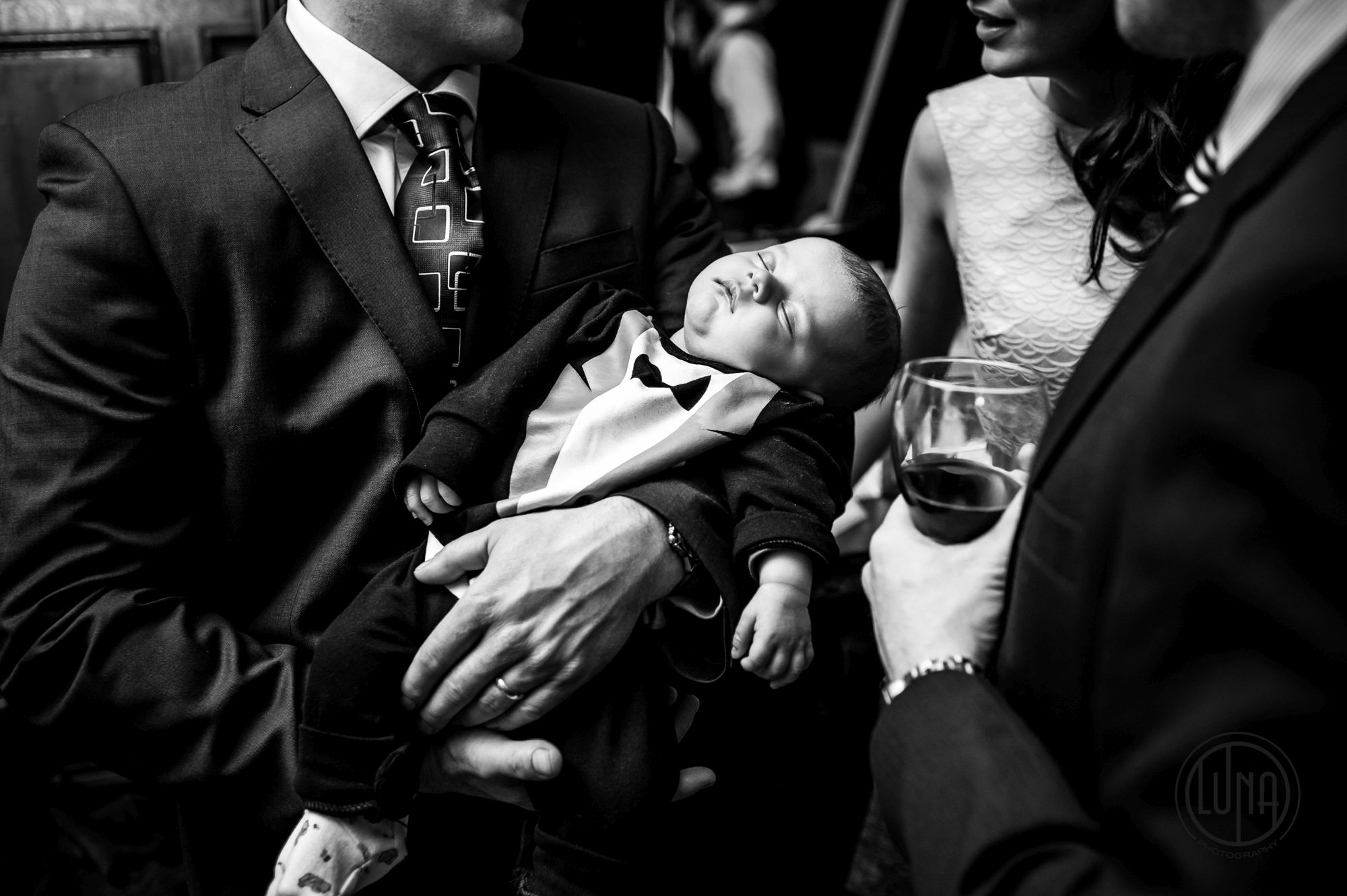 baby asleep in guests arms at wedding at huntsham court in devon