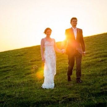 bride and groom walking during devon sunset wedding photography by luna weddings