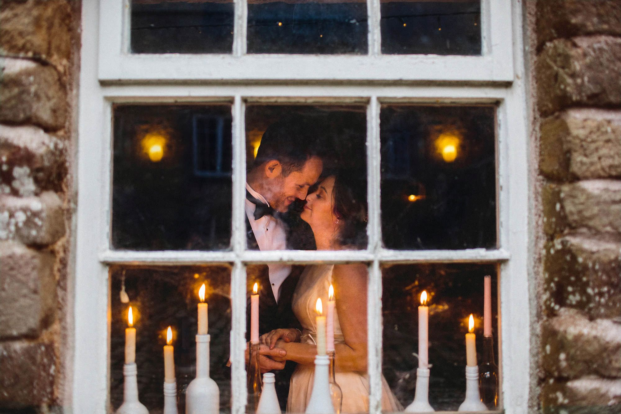 bride and groom behind window with candles - devon wedding photography by luna weddings