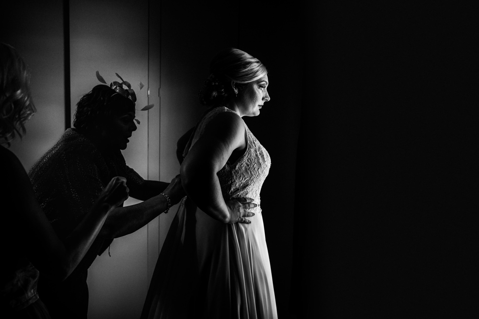 bride in nice light being helped into wedding dress, black and white image