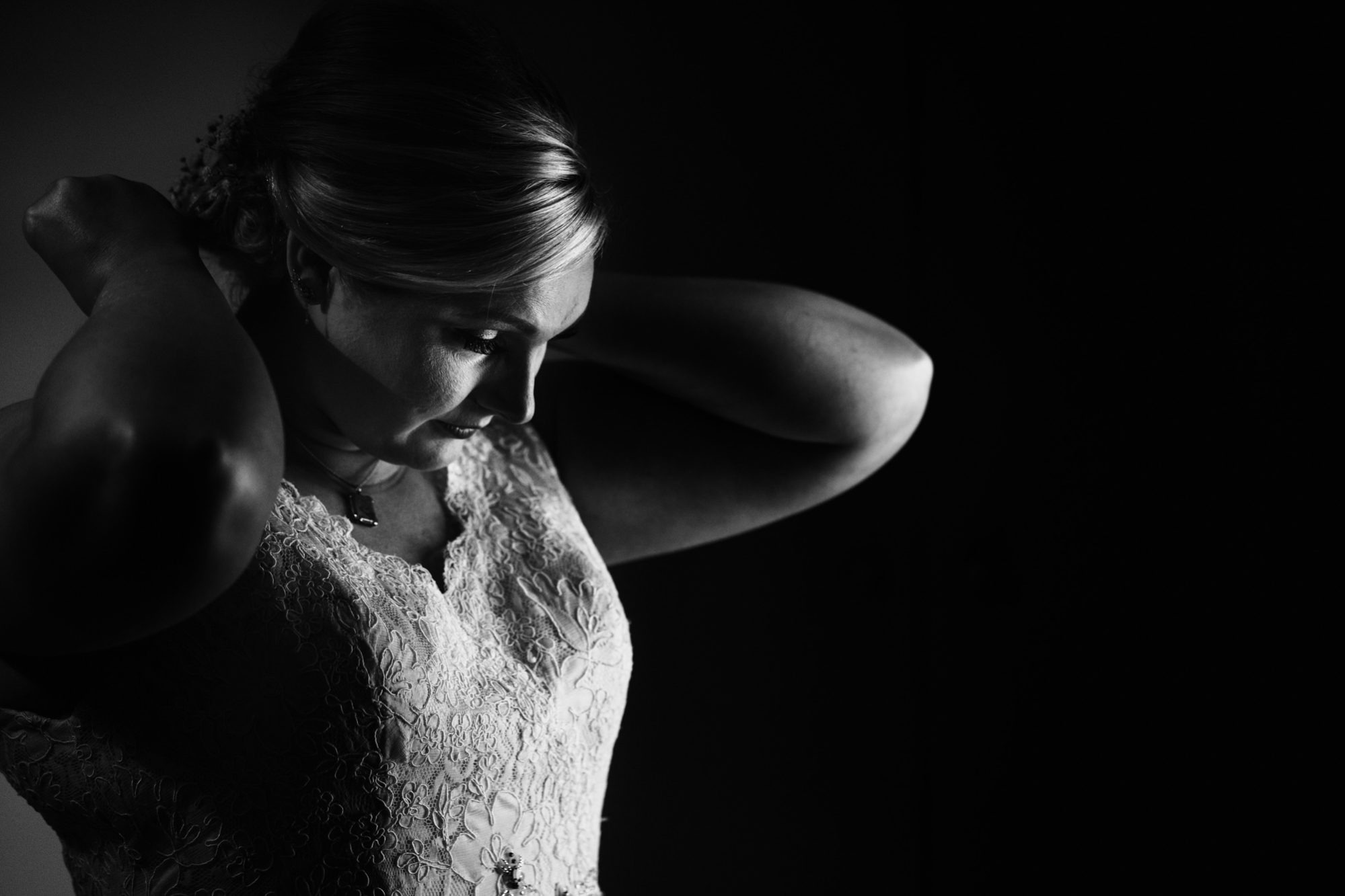 bride putting on necklace in nice light before wedding at stanway house