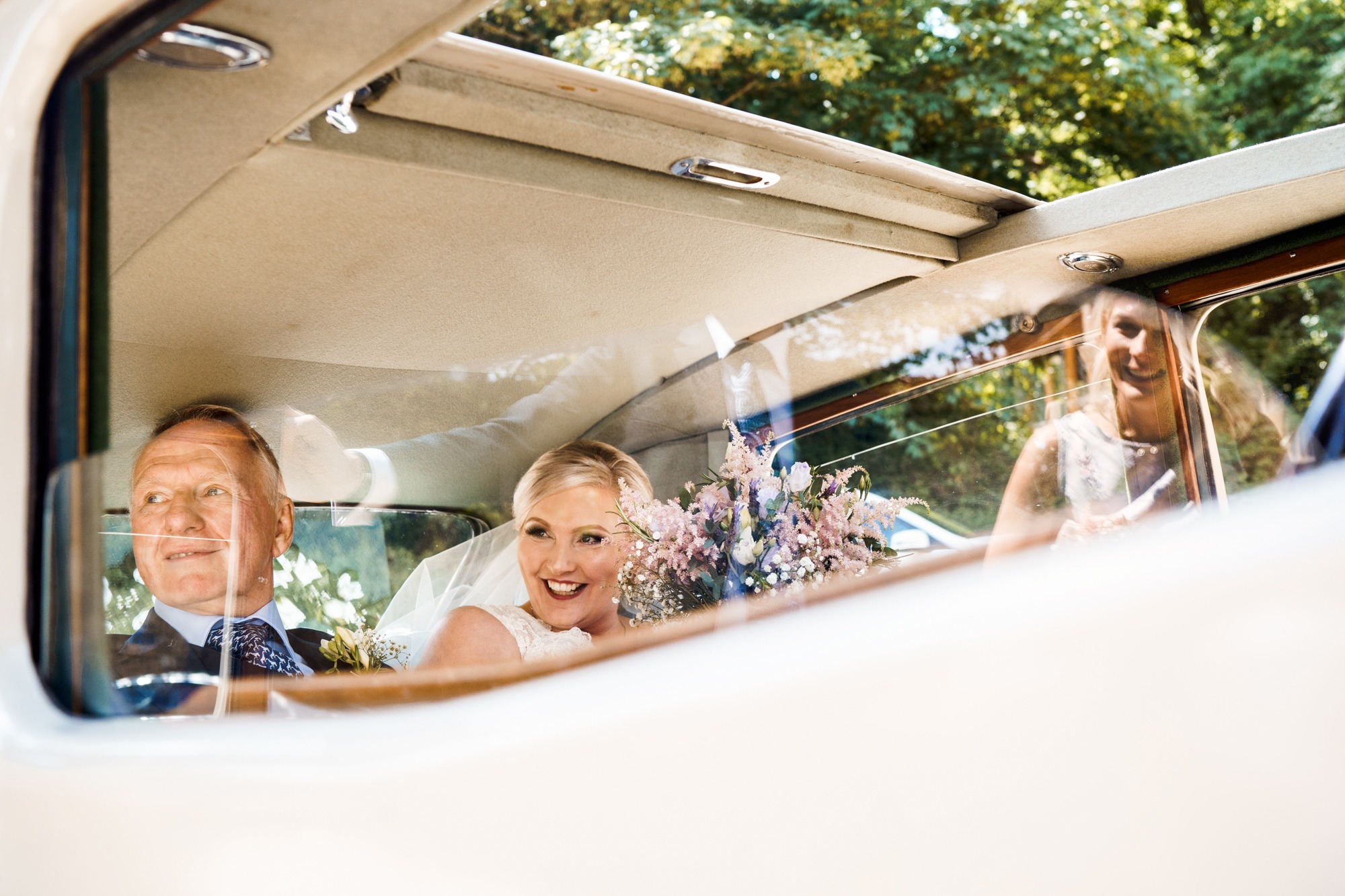 bride and father in car before ceremony, bridesmaid reflected