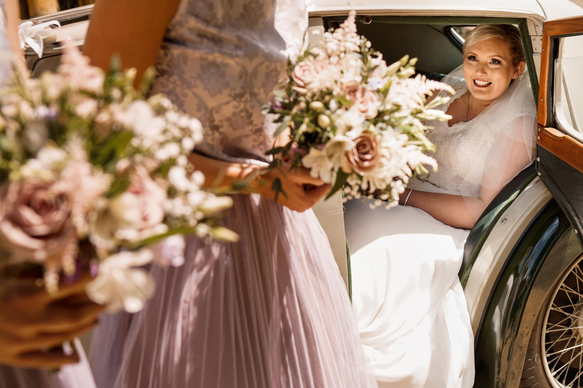 bride getting out of car shot through bridesmaids flowers