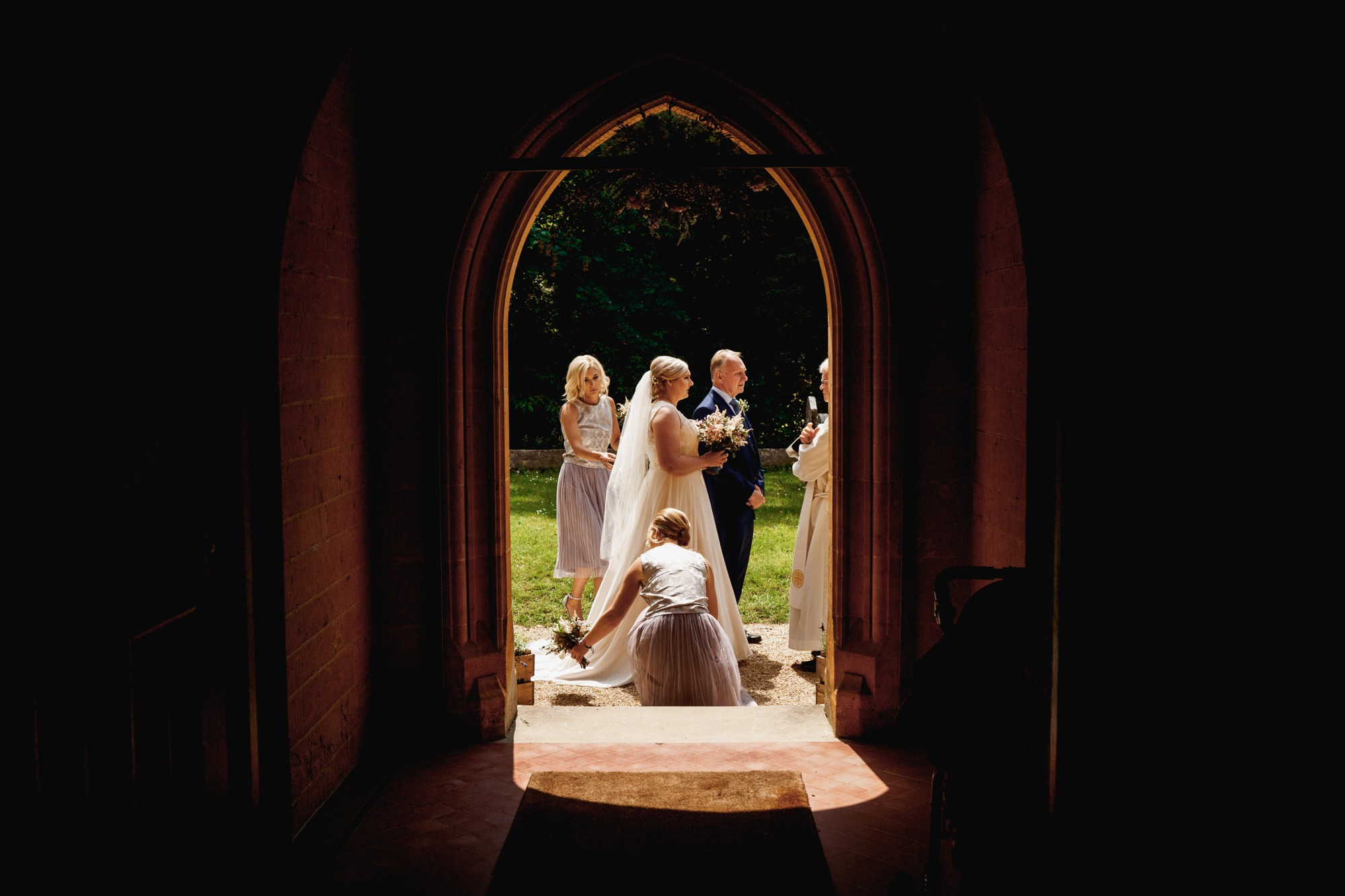 bride with her father and bridesmaids through church door before wedding ceremony