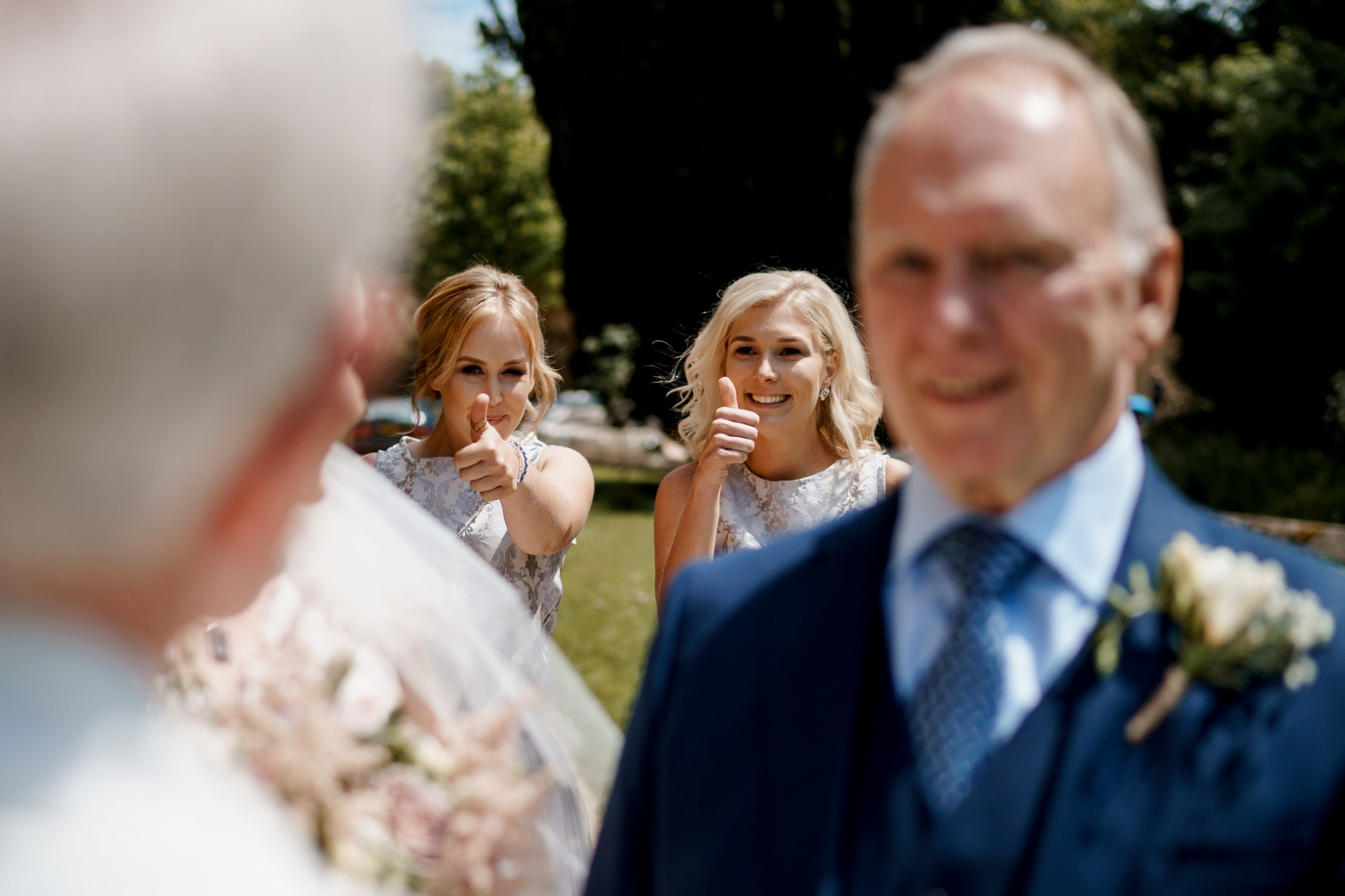 bridesmaids thumbs up to bride before wedding ceremony