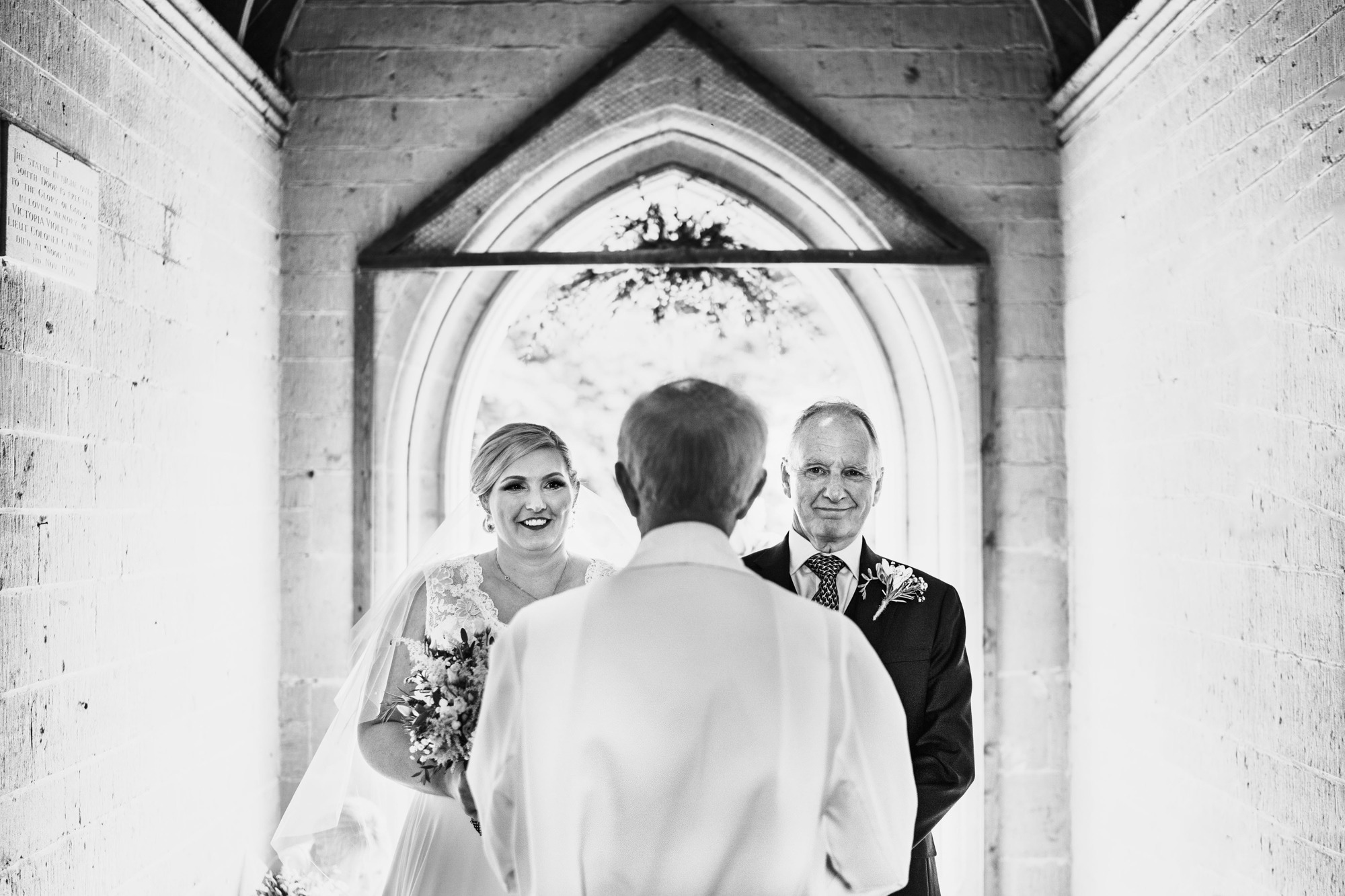 bride and father entering church in black and white