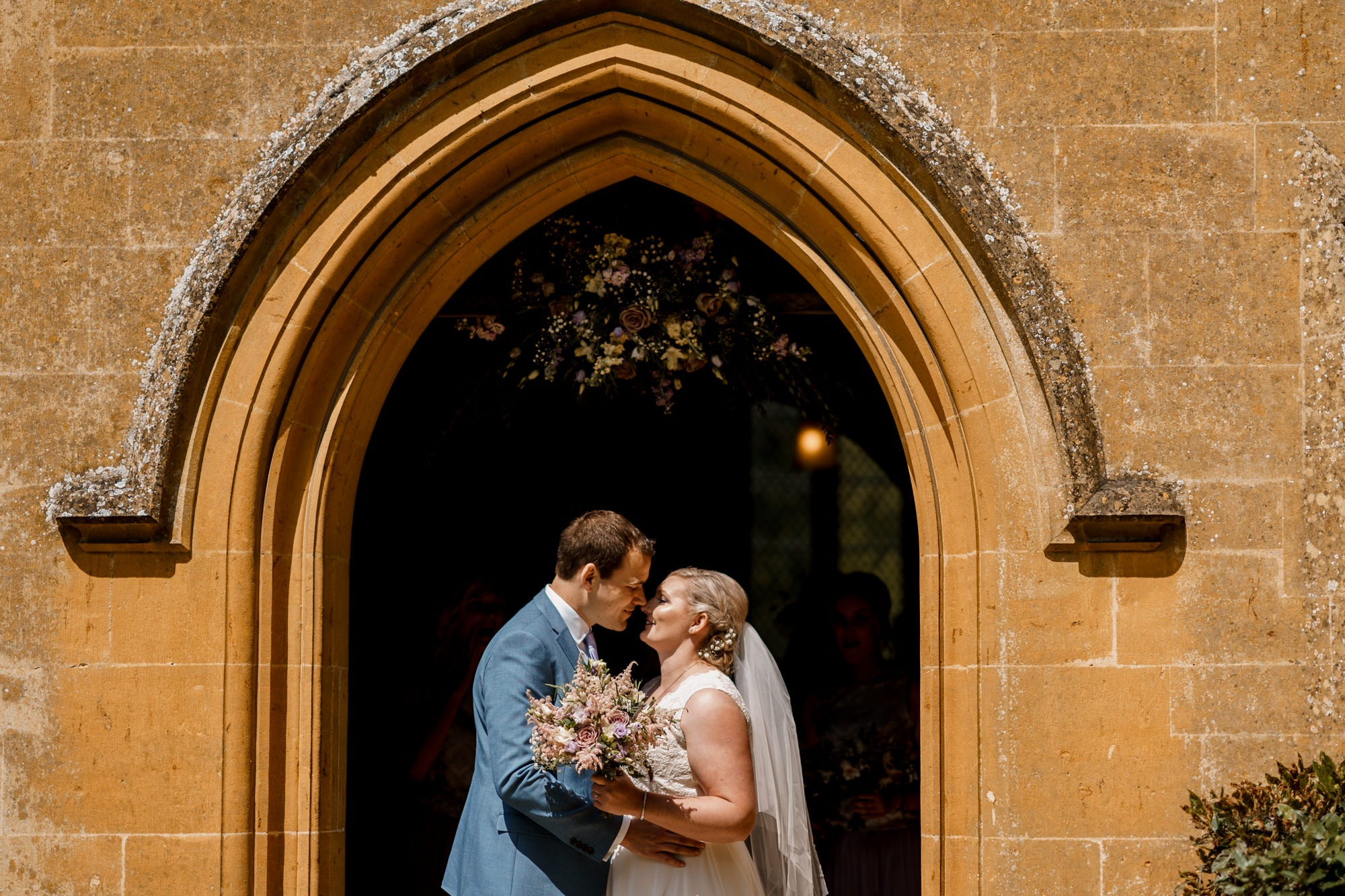bride and groom face each other in church doorway