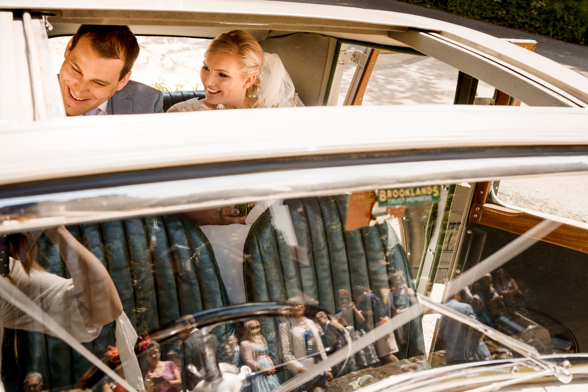 bride and groom in vintage car, guests reflected