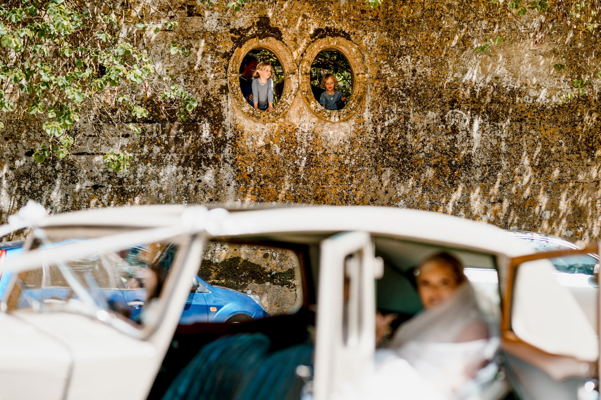 children in windows watching bridal car