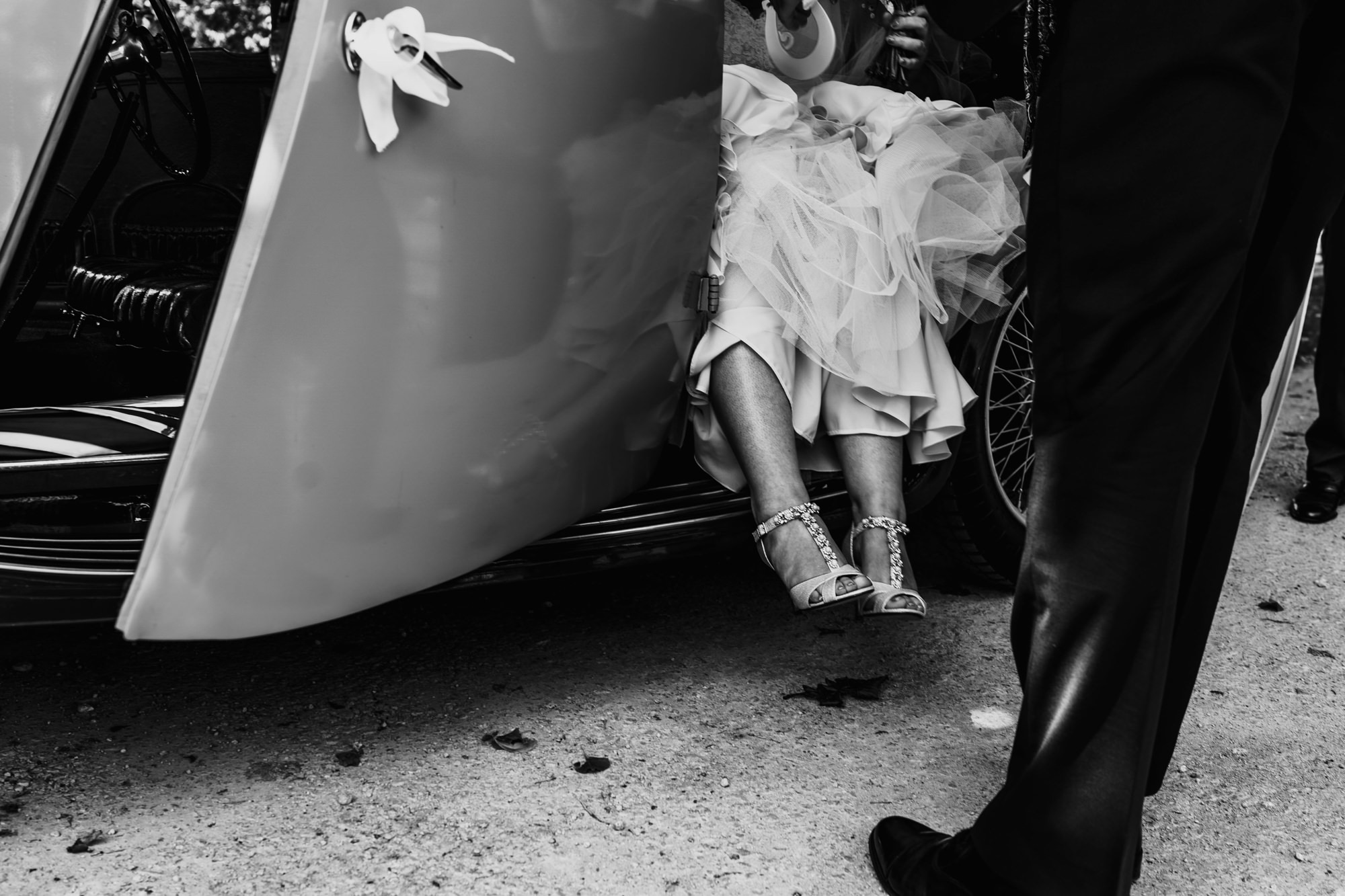 brides dress and shoes coming out of car in black and white