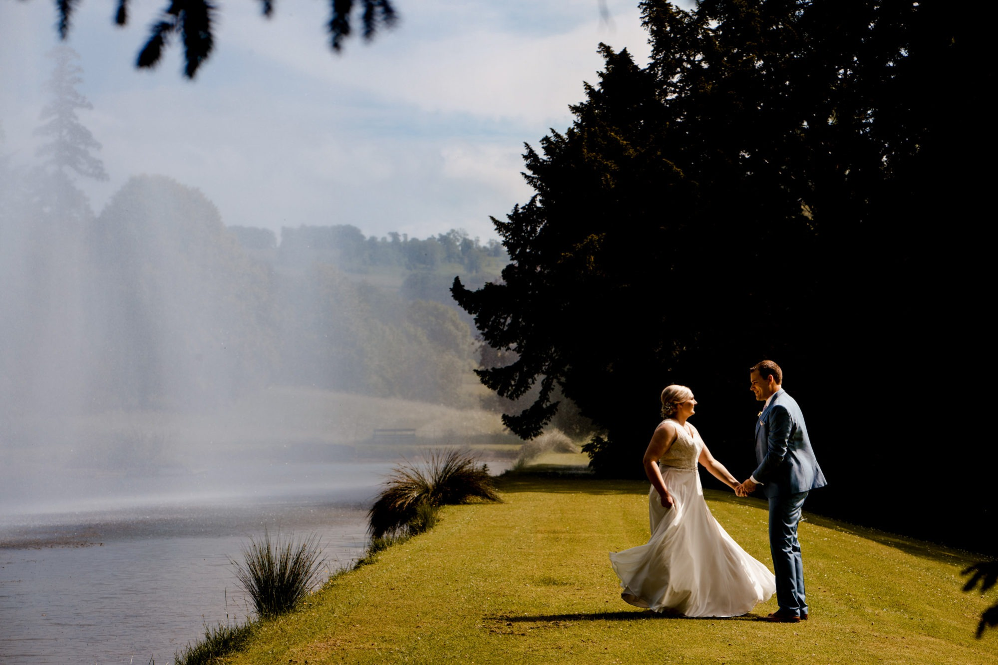 bride and groom with fountain at stanway house