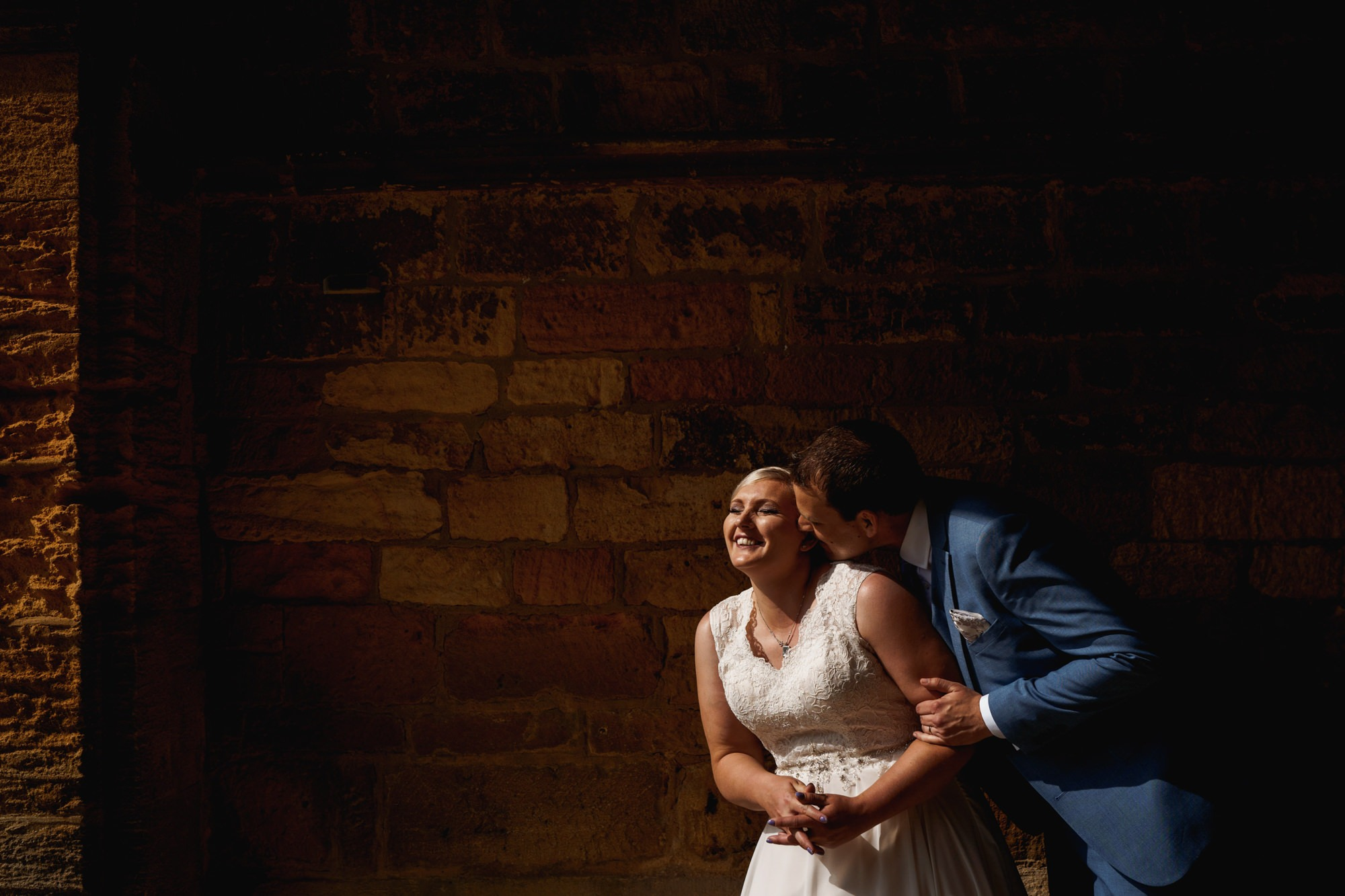 groom cuddles laughing bride at stanway house