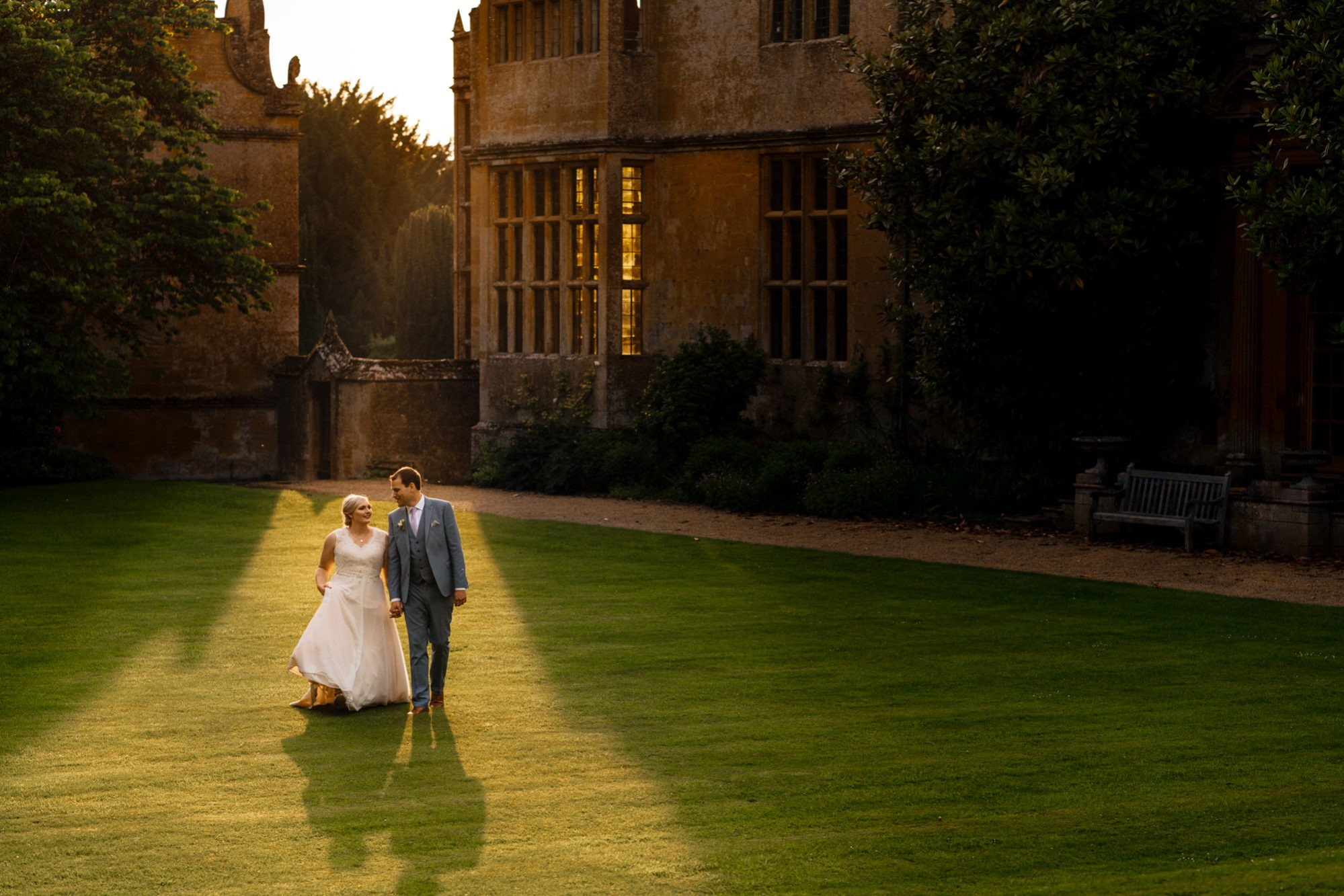 bride and groom walk in lovely light at stanway house