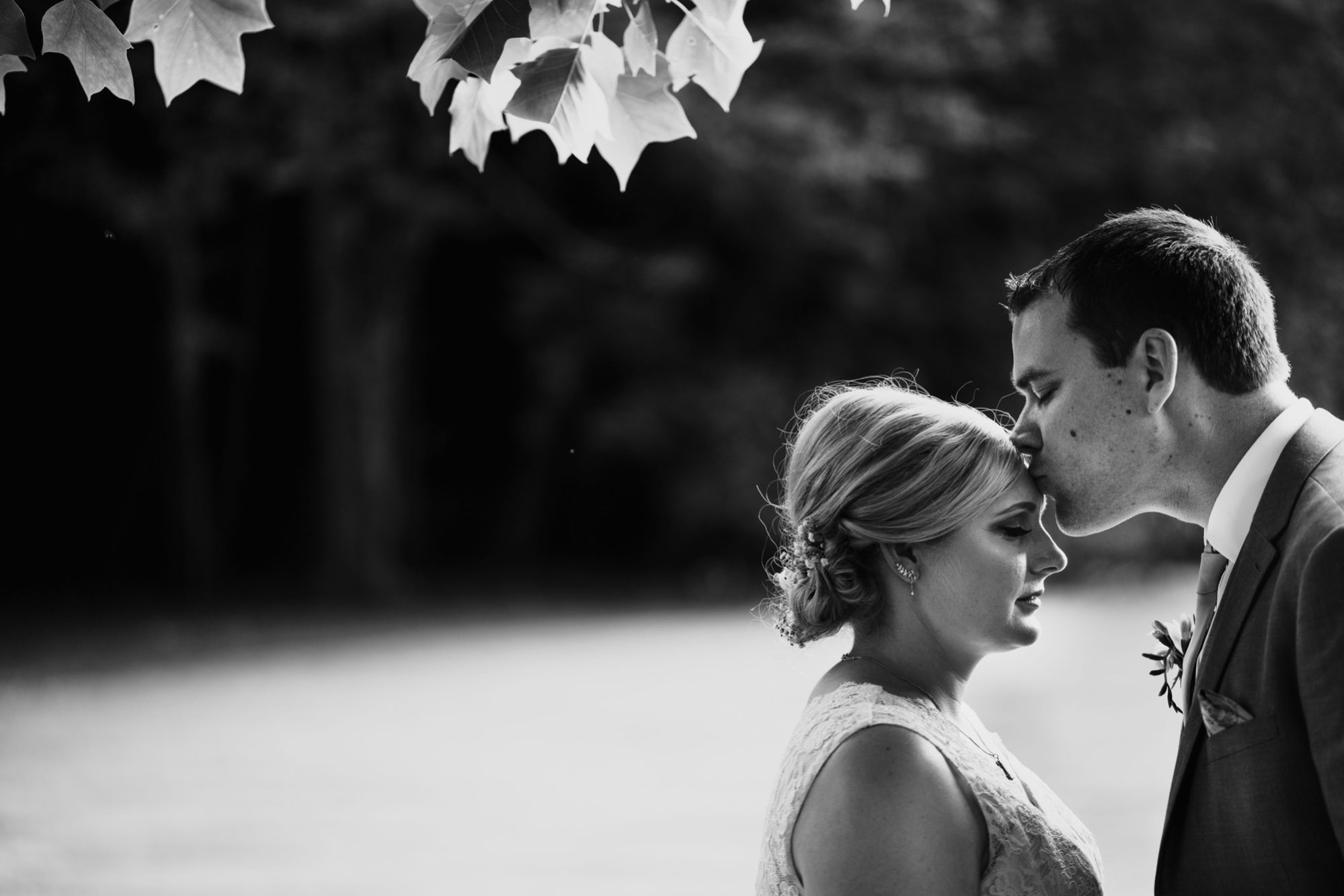 groom kisses brides forehead during stanway house wedding photography shoot