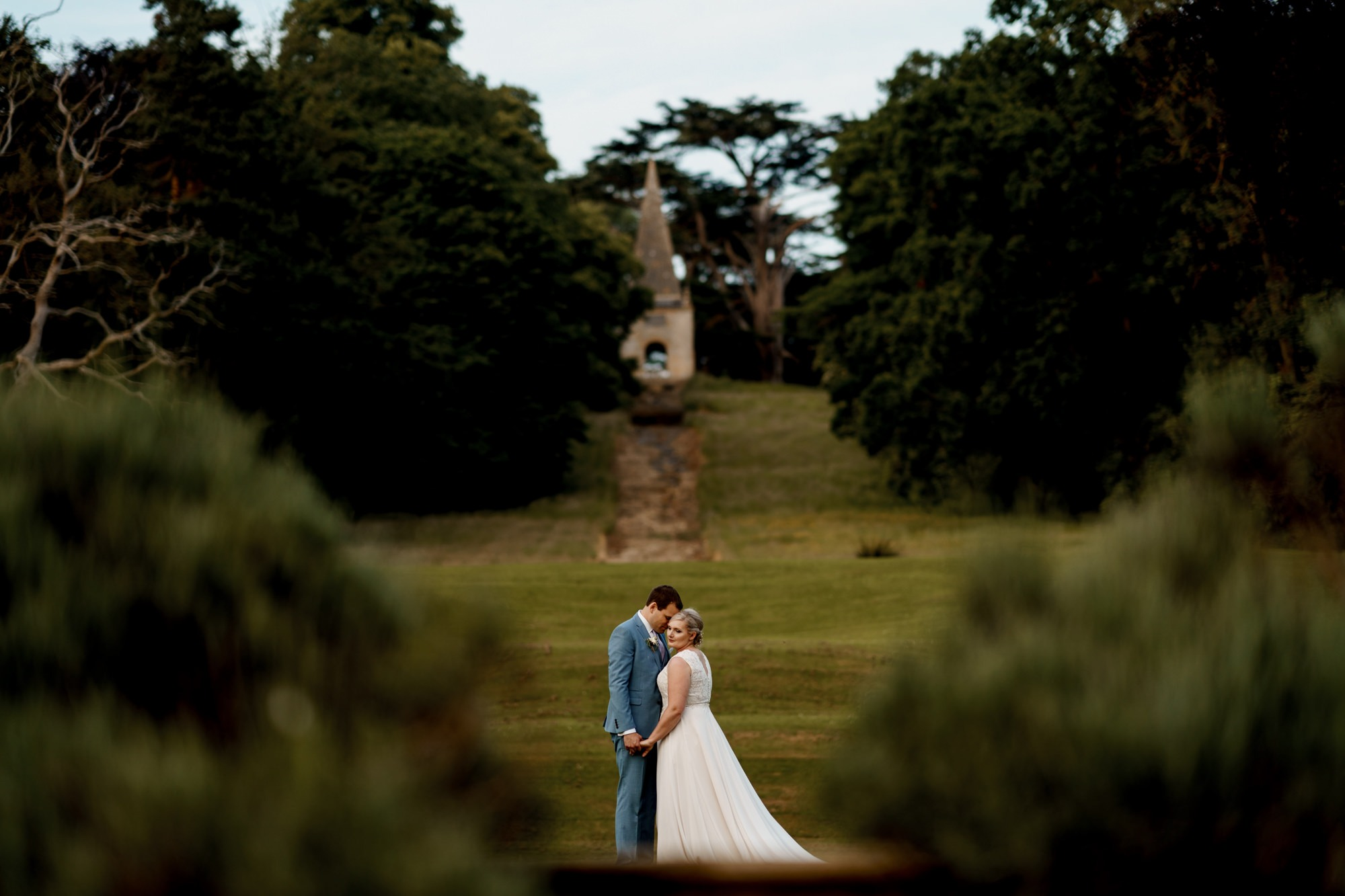 bride and groom stand together at stanway house in front of monument