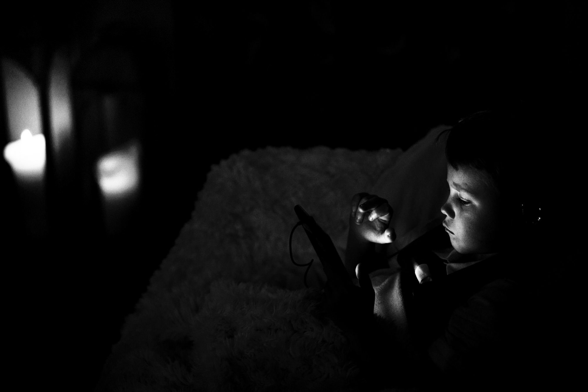 little boy on ipad with lit up face