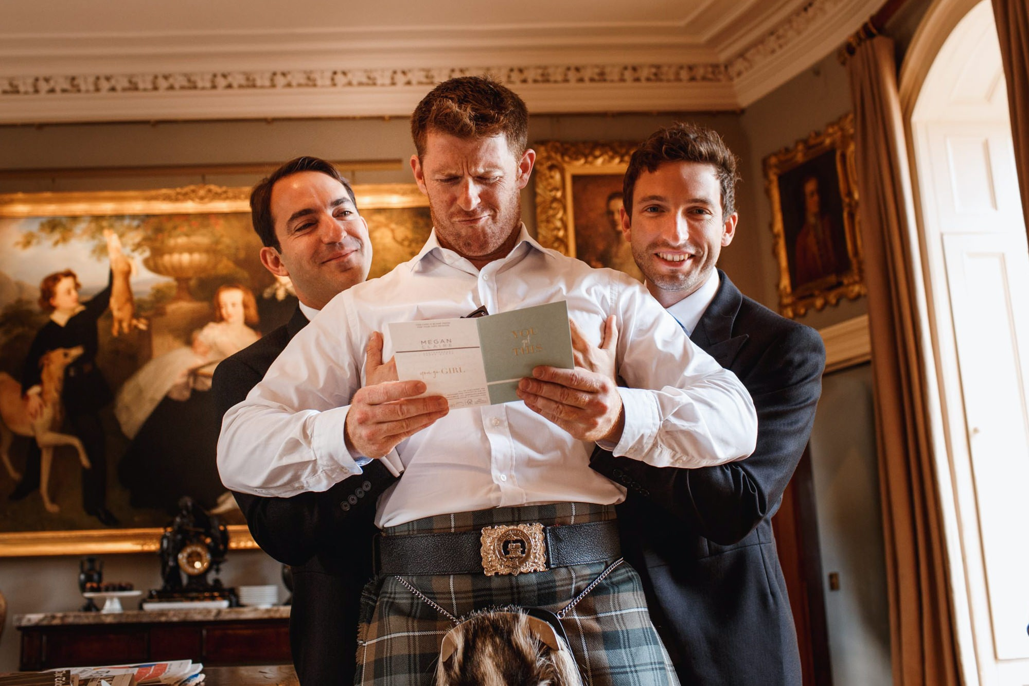 groom reading card before wedding at aldourie castle