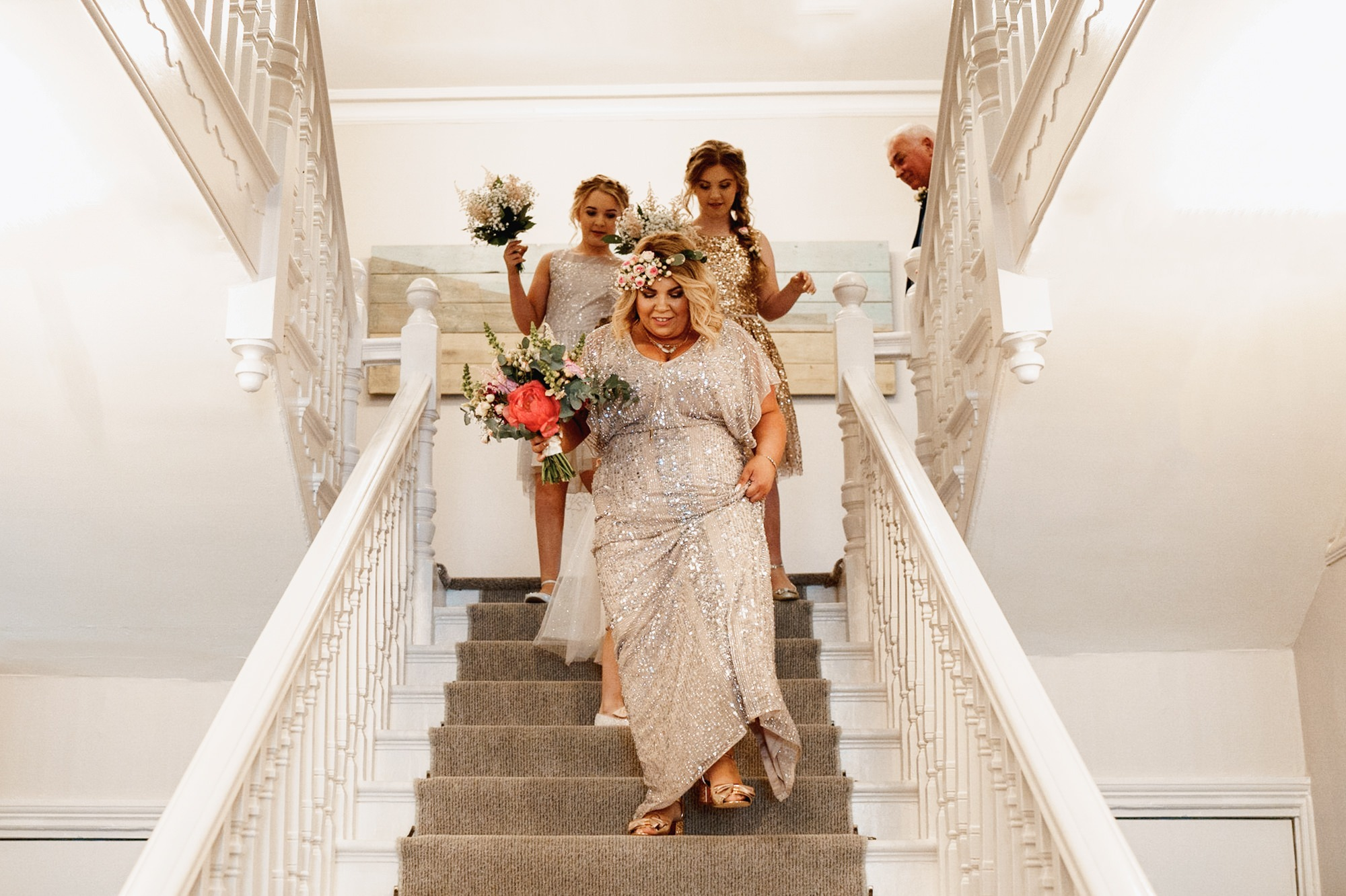 bride ad bridal party walk downstairs at watergate bay hotel wedding